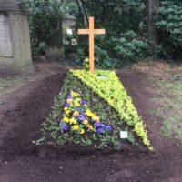 Einfache Grabstelle mit Holzkreuz