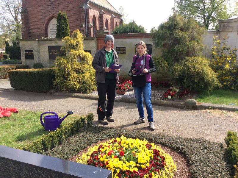 Kontrolle Dauergrabpflege vor einer Grabstelle mit hellleuchtender Frühjahrsbepflanzung