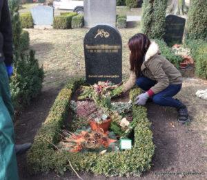 Grabschmuck auf die Grabstelle zurücklegen